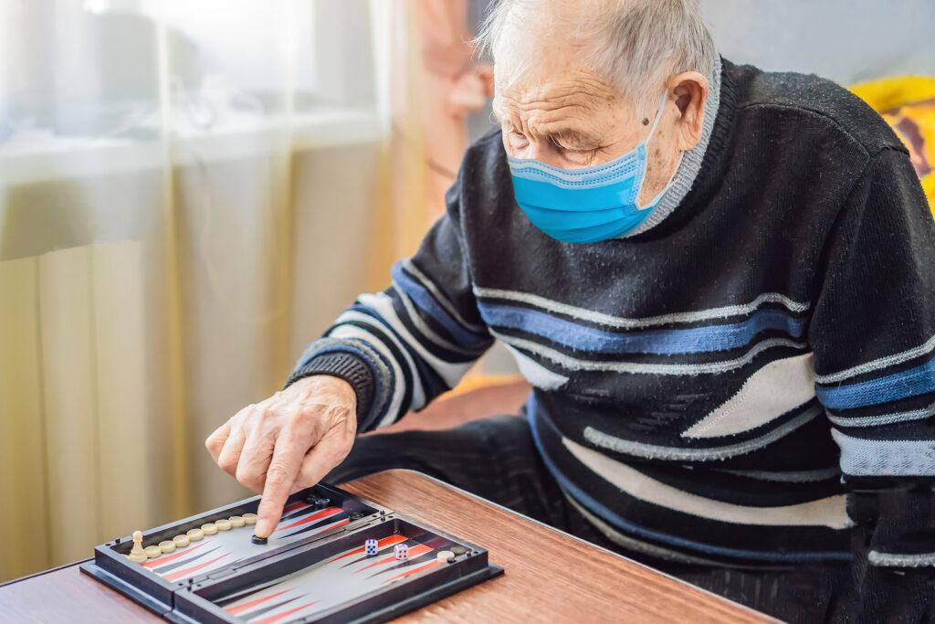 Senior man wearing a medical mask during COVID-19 coronavirus playing backgammon in a nursing home