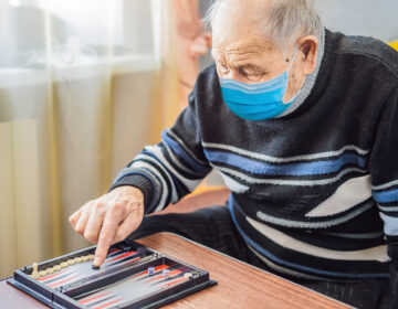 Senior man wearing a medical mask during COVID-19 coronavirus playing backgammon in a nursing home