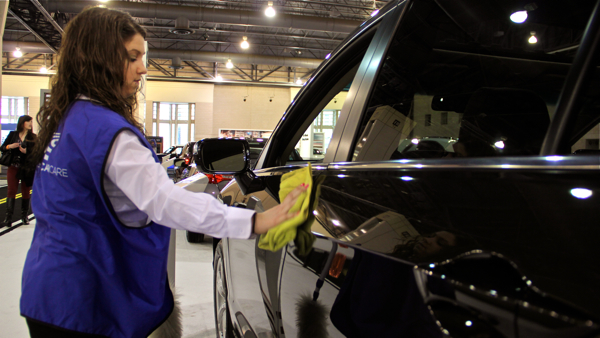 Auto show worker Stephanie Weitzenkern's job is to keep cars free of fingerprints and smudges left by visitors.