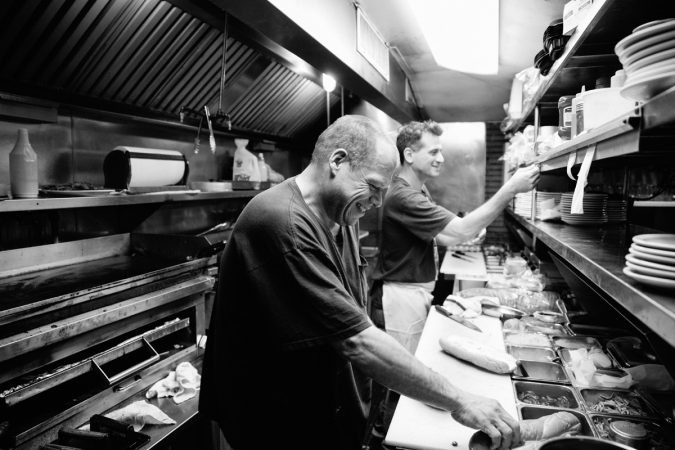 """Wayne has been a cook at Little Pete's for more than 14 years. He says, """"I've seen everything in here."""" (Neal Santos/WHYY)"""