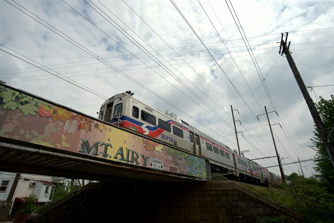 A SEPTA train on the Chestnut Hill West line crosses Mt Pleasant Avenue as it is on its way to Center City. The trestle is part of the Mural Arts Program and made possible with support of Mt Airy residents, (including Ken Weinstein). (Bastiaan Slabbers for WHYY)