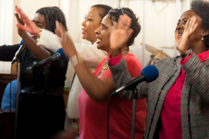 Sister Veta Coleman and others lead the congregation in song during Sunday morning service.