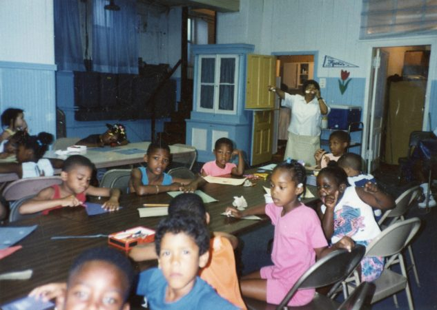 Neighborhood kids do arts and crafts at a makeshift community center in the basement of Disney Church in Jewtown. The parents of the community worked tirelessly to keep their children busy, productive and safe despite having little money. (Courtesy of Diane Precht)
