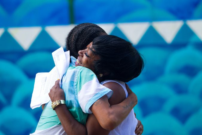 Storytellers Faith Bartley and Michelle Scales embrace during the performance. (Miguel Martinez/Every ZIP Philadelphia)