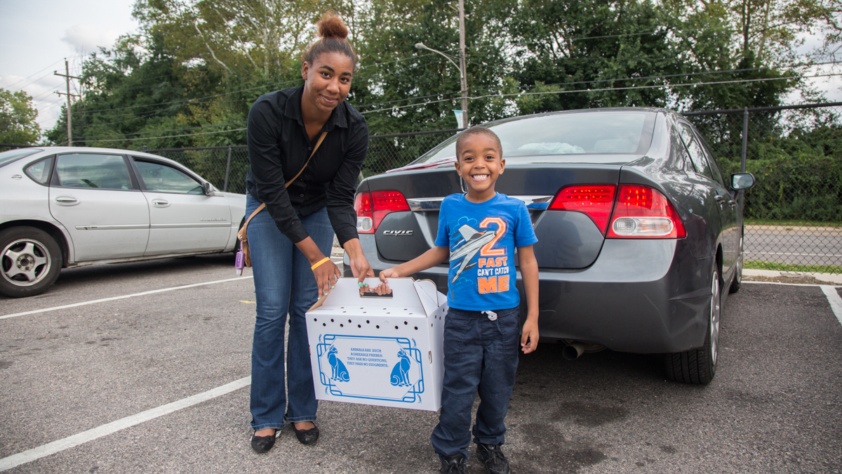 Kiera Fletcher, of Levittown, poses with her son Devante, 3, and the box that holds their new kitten. (Emily Cohen for WHYY)