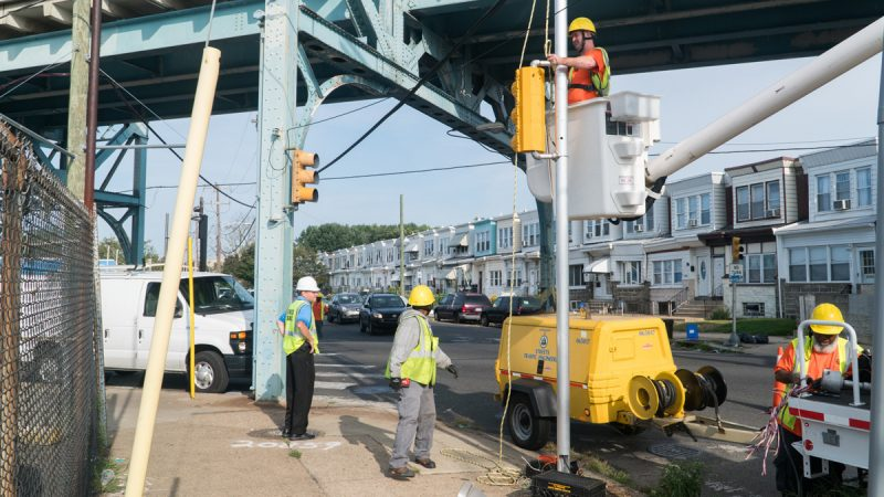 The Streets and Traffic team works above and on the ground to repair a signal. (Branden Eastwood for WHYY)