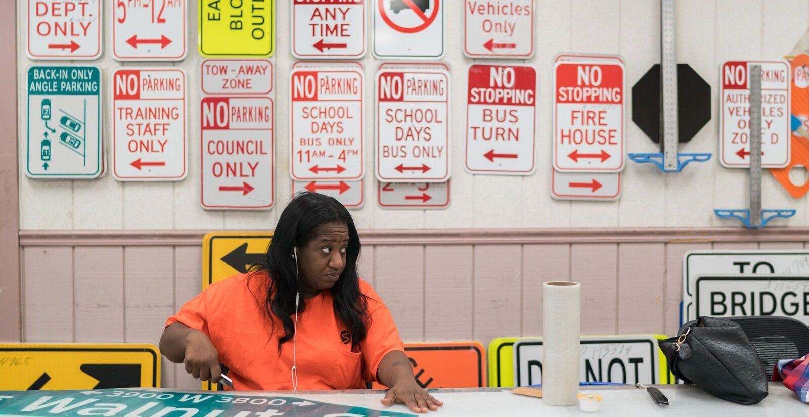 Marquita Alleyne cuts out a street sign at the Traffic Signal and Sign Shop. (Branden Eastwood for WHYY)