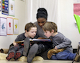 a teacher reads to two children