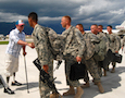 Army servicemen are greeted by a veteran