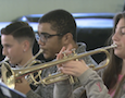 a trio of students play trumpets