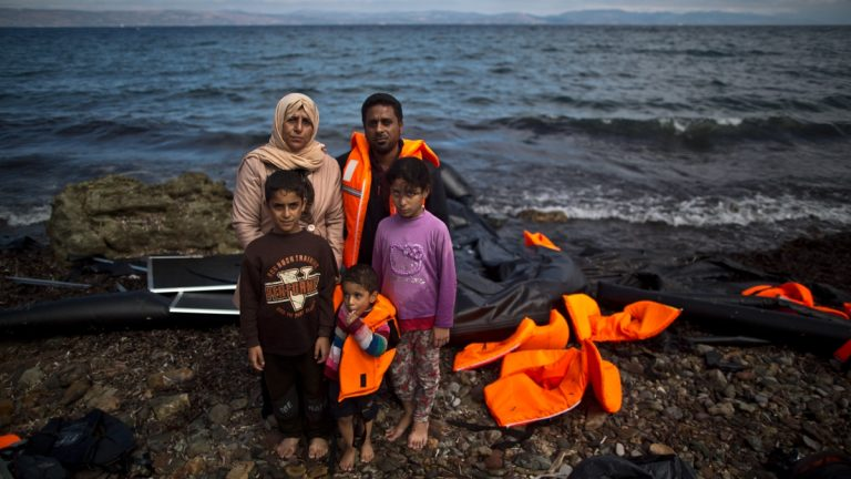 """Iraqi refugee Mohammed Sadoun, 39, and his wife Suhad, 35, who came from Mosul, Iraq, pose for a picture with their children shortly after arriving on a dinghy from the Turkish coast to the northeastern Greek island of Lesbos. """"We had to run from Islamic State, IS, death will reach us all if we don't. I wish to reach Germany where humanity exists, and my children will grow up with a bright future,"""" Mohammed Sadoun said. (AP Photo/Muhammed Muheisen)"""