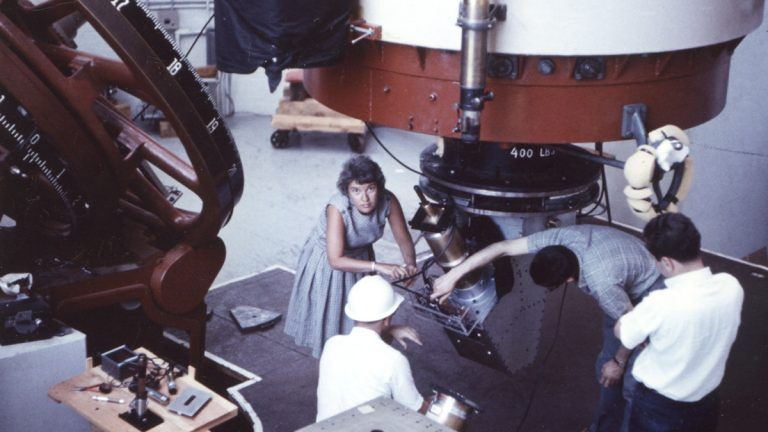 Vera Rubin at Lowell Observatory in 1965. Kent Ford, her longtime collaborator is kneeling in the hard hat. (Photo by Bob Rubin)