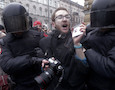 Riot policemen detain a journalist during a protest rally in St.Petersburg, Russia