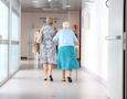 two women walk down a hospital hallway