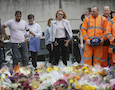 City workers and others stand after laying flower tributes in the London Bridge area of London