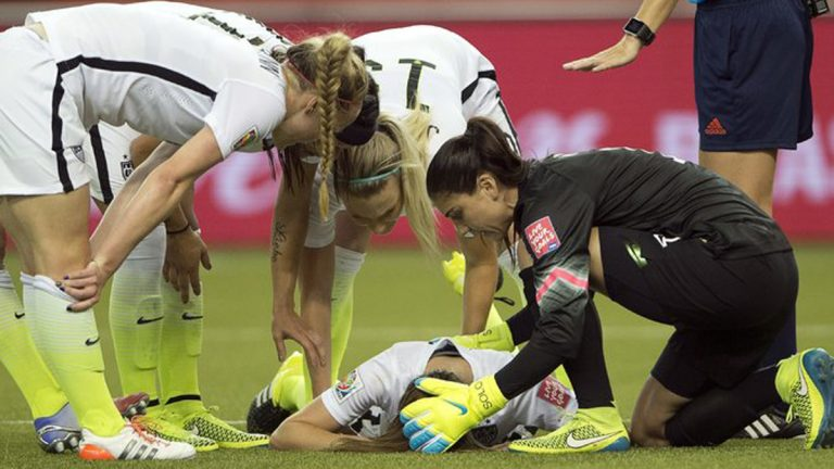 Teammates tend to Morgan Brian, who collided with Alexandra Popp of Germany during the Women's World Cup semifinal on Tuesday. (Ryan Remiorz/The Canadian Press, via Associated Press)