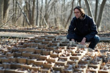 Local artist and professor Jake Beckman with his degradable art structure at the Schuylkill Center for Environmental Education in Roxborough. (Bastiaan Slabbers/for NewsWorks)