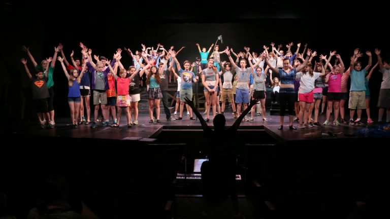 The cast of 'Children of Eden' raise their hands during a rehearsal at Wolf Performing Arts Center in Wynnewood. (Peter Crimmins/WHYY)