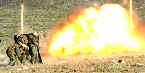 Marines from Combat Engineer Platoon, Marine Wing Support Squadron 473 blow a hole in a fence at Hawthorne Army Weapons Depot in Nevada on June 17, 2010 during demolitions training for exercise Javelin Thrust 2010. The Marines used a kevlar blanket to shield themselves from fragmentation and to reduce the impact of the blast. (Photo by Pfc. Nana Dannsaappiah)