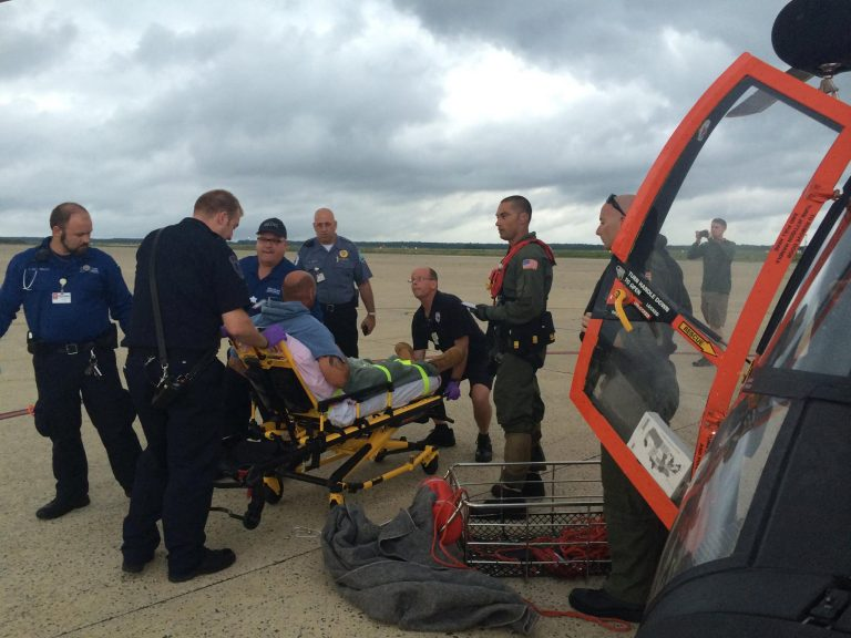 An MH-65 Dolphin helicopter crew from Air Station Atlantic City, N.J., transfers a man to local emergency medical services personnel, at the air station, July 15, 2014. The aircrew medevaced the man from a fishing boat about 45 miles off shore from Ocean City, Maryland, after the man experienced health issues. (U.S. Coast Guard photo)
