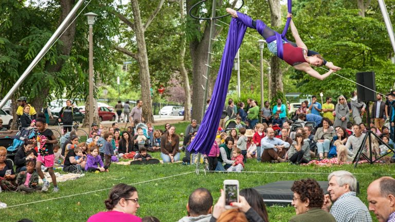 Nina Giacobbe takes to the silks during her performance with Tangle Arts in Clark Park. (Emily Cohen/for NewsWorks)