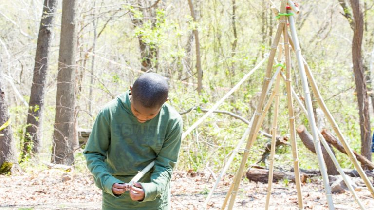 A child uses Stick-lets to build an outdoor structure. (Photo courtesy of Christina Kazakia)