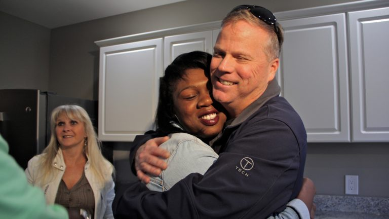 Army veteran and single mother Janne Dawson hugs Gary Smith,  a Mullica Hill contractor who bought and renovated an abandoned home in Camden and gave it to her through Catholic Charities. (Emma Lee/WHYY)