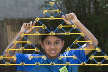 Anjay Bhatt shows off a Sierpinski Triangle created  with K'NEX. His triangle was a piece of the larger 45 by 90 foot triangle built in  yard of the Wagner Free Institute of Science. (Jonathan Wilson For Newsworks)