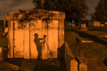 A photographer's shadow is cast against the wall of a mausoleum from the illumination of street lights. (Jonathan Wilson for Newsworks)