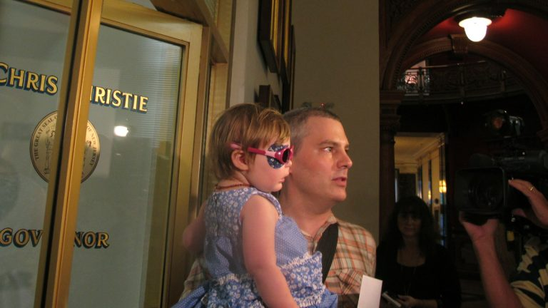 Brian Wilson, of Scotch Plains, N.J. holds his 2-year-old daughter Vivian as they prepare to deliver boxes of letters to Gov. Chris Christie's office in Trenton, N.J., on Thursday, Aug. 1, 2013. (Geoff Mulvihill/AP Photo)
