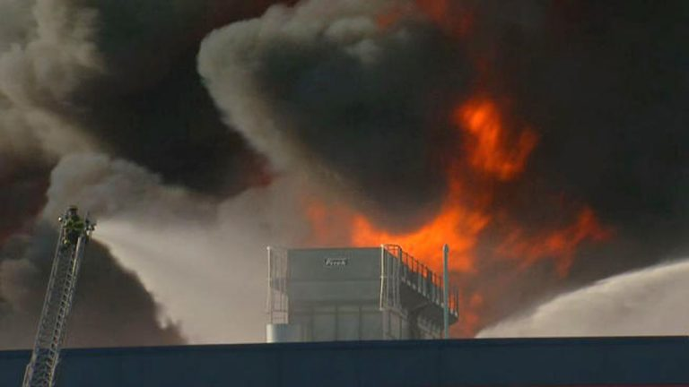 Firefighter battles flames billowing into the sky at the Dietz & Watson deli meat storage facility in Delanco, Burlington County, N.J. (Photo by NBC10)