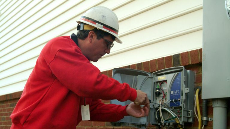 A Verizon technician installs a device, known as an optical network terminal (ONT), as part of the installation of all-fiber FiOS Internet and FiOS TV at a customer's house.(AP Photo/Verizon)