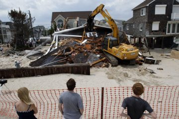 People watch from the beach Wednesday, July 10, 2013, as a home severely damaged by Superstorm Sandy is demolished in the Normandy Beach section of Toms River, N.J. (Mel Evans/AP Photo, file)