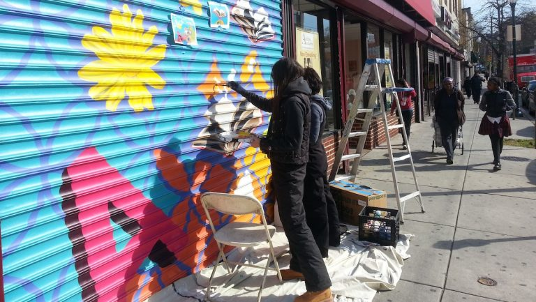 Kala Hagopian and Ali Williams painting the Acclaim Academy grates in Germantown. (Aaron Moselle/WHYY)