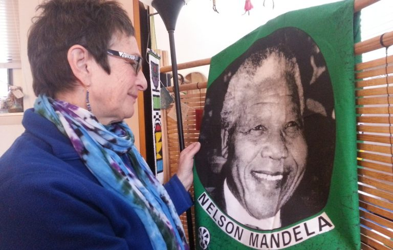 Marilyn Cohen looks fondly at a piece of Nelson Mandela memorabilia from her years in South Africa. (Aaron Moselle/WHYY)