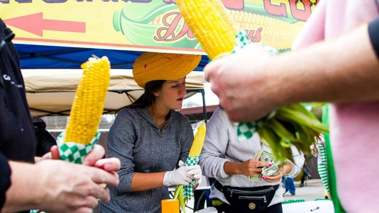 Jess Patrone serves roasted corn at the 'The Corn Lady' stand at the 2013 Manayunk StrEat Food Festival (Brad Larrison/for NewsWorks, file)
