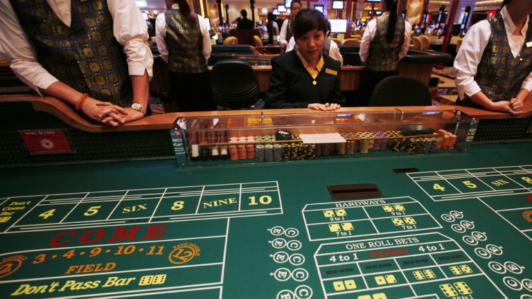 Casino workers stand at gaming tables inside the Sands Cotai Central, in Macau. (AP Photo/Kin Cheung)