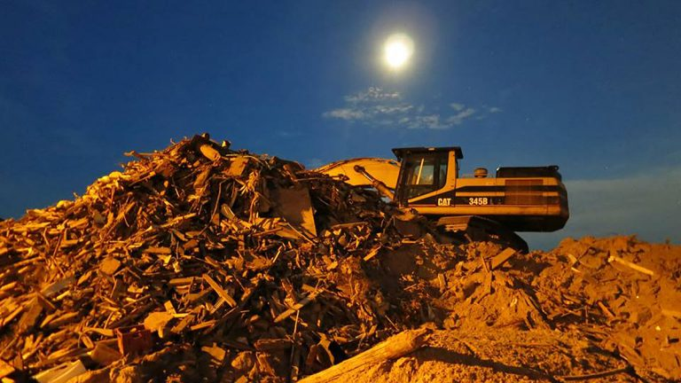 An excavator sits atop debris from Superstorm Sandy in Mantoloking. (Alan Tu/WHYY)