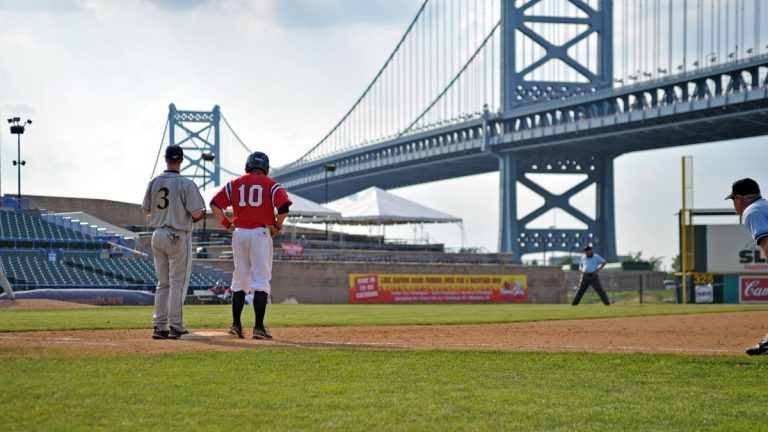 Dayton baseball player Mel Skochdopole (No. 10) stands on first base in an Atlantic 10 tournament game, with the Ben Franklin Bridge in the background on May 25, 2011 in Camden, N.J. (Photo via Shutterstock)