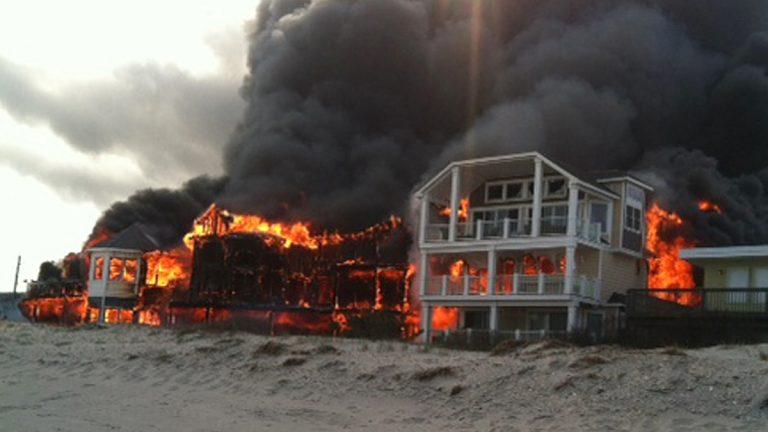 Fire engulfs three homes near the beachfront, Friday, April 18, 2014, in Sea Isle City, N.J.  (AP Photo/Joanne Dollarton)