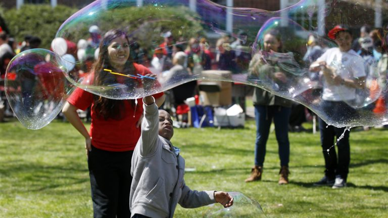 Children play with huge bubbles during the Rutgers Day events in New Brunswick, N.J., Saturday, April 26, 2014.  (AP Photo/Mel Evans)
