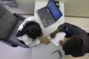 At a health center in Trenton, Rachael Richardson, (left), helps Louis Peters to sign-up for a new health insurance plan (Mel Evans/AP Photo)
