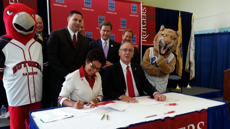 Rutgers Camden Chancellor Phoebe Haddon signs the agreement Monday. (Tom MacDonald/WHYY)