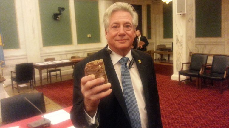 Philadelphia Councilman Dennis O'Brien displays a brick from a vacant building where two city firefighters were killed in 2012. He's proposing a task force to inspect empty facilities and note floor plans and other details that could prove important in time of emergency. (Tom MacDonald/WHYY)