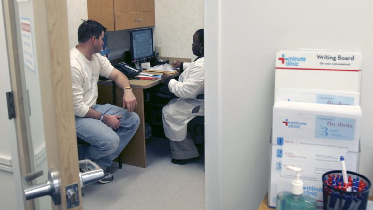 Shanda Johnson, right, a nurse practitioner, interviews patient Bill Gilligan at a MinuteClinic at the CVS drug store in North Brunswick, N.J., (AP Photo/Mike Derer)