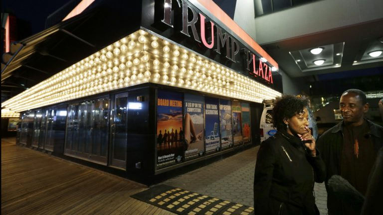 Ruth Hardrick, a dealer who worked at Trump Plaza Hotel & Casino for 26 years, stands with friend, Anthony Powell, on The Boardwalk, as she answers a question after the casino closed early Tuesday, Sept. 16, 2014. (AP Photo/Mel Evans)