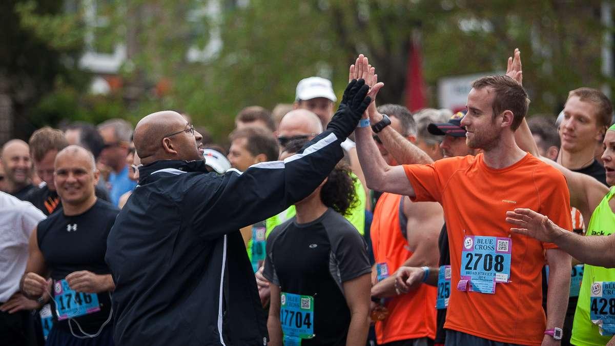 Philadelphia Mayor Michael Nutter high fives runners before the start of the 2014 Broad Street Run. (Brad Larrison/for NewsWorks)