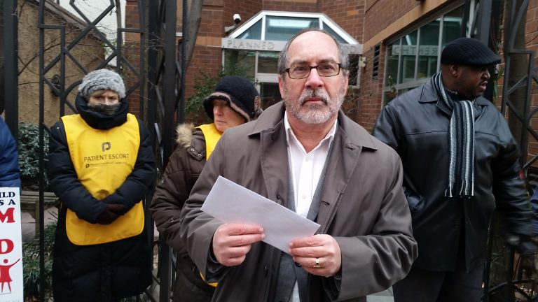 The Rev. Patrick Mahoney, near the entrance to the Planned Parenthood facility at 1144 Locust Street in Philadelphia, holds a letter asking for an abortion moratorium. (Tom MacDonald/WHYY)