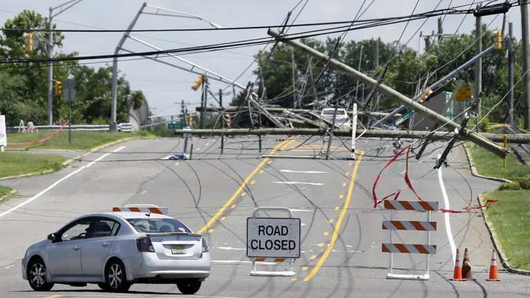 A driver turns her car at a closed road on June 24, 2015 after a violent storm downed poles and power lines  in Gibbstown, N.J. (AP Photo/Mel Evans)