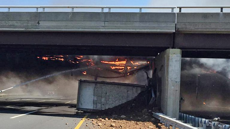 In this photo taken Tuesday, Aug. 4, 2015, and provided by the New Jersey State Police, a fire burns around a dump truck after it hit the South Wood Avenue overpass and overturned in Linden, N.J. (AP Photo/Sgt. Jeremy Micewicz, New Jersey State Police via AP)